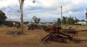 Old farm machinery with visiting caravans in the background