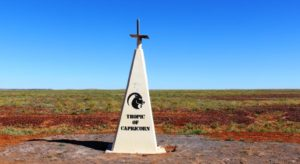 The marker for the Tropic of Capricorn sits by the road where it crosses a treeless plain