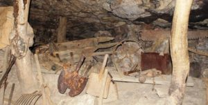 A display of mining tools in an area where the roof is supported by local timber.