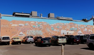 An impressive mural adorns a wall of a prominent building
