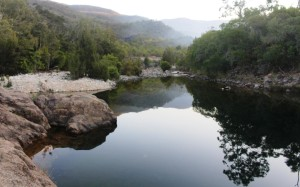 The tranquil waters of Crystal Creek with smoke from a mountain fire in the background