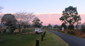 A cloud bank illuminated by the sun rise behind the camping area
