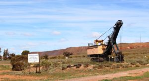 """A """"retired"""" excavator against the background of mine overburden at Iron Knob"""